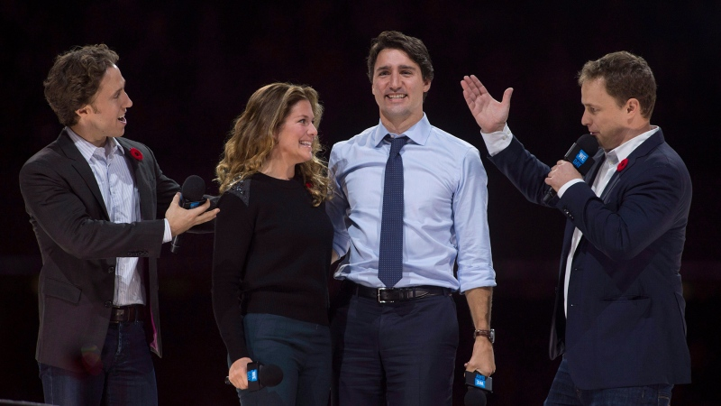 Co-founders Craig (left) and Marc Kielburger introduce Prime Minister Justin Trudeau and his wife Sophie Gregoire-Trudeau as they appear at the WE Day celebrations in Ottawa, Tuesday November 10, 2015. THE CANADIAN PRESS/Adrian Wyld