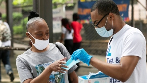 In this July 8, 2020, file photo, Stephane Labossiere, right, with the Mayor's Office of Immigrant Affairs, hands out masks and printed information about free COVID-19 testing in New York. (AP Photo/Mark Lennihan, File)