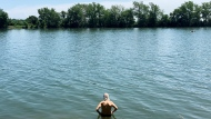 A man beats the heat while wading next to the Saint-Lawrence River during a heat-wave in Montreal, Friday, July 10, 2020. THE CANADIAN PRESS/Graham Hughes