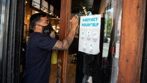 Owner Ankur Vadhera wipes the front door's touch points with sanitizer after a person exited at Capital Barber Shop in Ottawa, on its first day of reopening as Ontario moves into Stage 2 of its plan to lift lockdowns implemented in response to the COVID-19 pandemic, on Friday, June 12, 2020. THE CANADIAN PRESS/Justin Tang