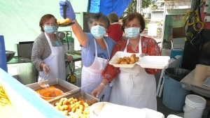 Women serve food at Greek Summerfest in East Vancouver on July 12, 2020.