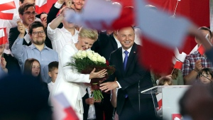 Incumbent President Andrzej Duda and his wife Agata Kornhauser-Duda smile after receiving flowers from supporters in Pultusk, Poland, Sunday, July 12, 2020. (AP Photo/Czarek Sokolowski)