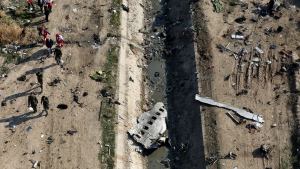 FILE - In this Jan. 8, 2020 file photo, rescue workers search the scene where a Ukrainian plane crashed in Shahedshahr, southwest of Tehran, Iran. Iranian investigators are blaming a misaligned missile battery and miscommunication between soldiers and their commanders for the Revolutionary Guard shooting down the Ukrainian jetliner in January, killing 176 people. The report released late Saturday, July 11, 2020 by Iran's Civil Aviation Organization comes months after the crash. (AP Photo/Ebrahim Noroozi, File)