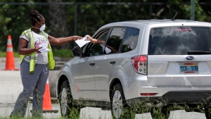A worker passes out forms to motorists as they drive up for a COVID-19 test at the Orange County Convention Center Sunday, July 12, 2020, in Orlando, Fla. Florida on Sunday reported the largest single-day increase in positive coronavirus cases in any one state since the beginning of the pandemic. (AP Photo/John Raoux)