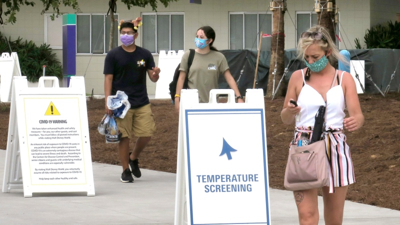 Guests wear masks as required as they arrive to attend the official reopening day of the Magic Kingdom at Walt Disney World in Lake Buena Vista, Fla., Saturday, July 11, 2020. (Joe Burbank/Orlando Sentinel via AP)
