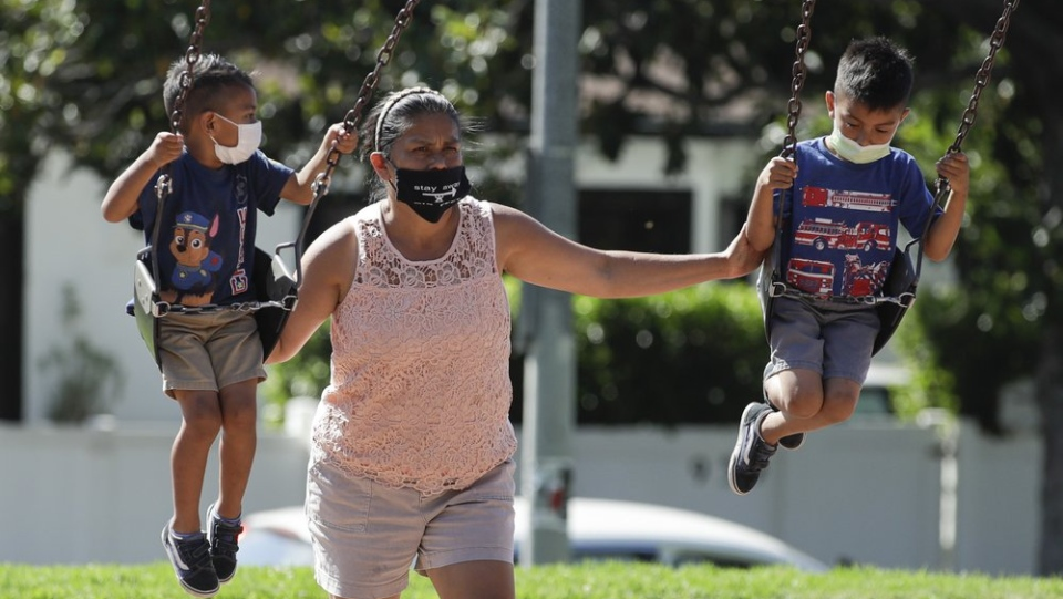 A woman and two children wear masks at a playground, Saturday, July 11, 2020, in Los Angeles. (AP Photo/Marcio Jose Sanchez)