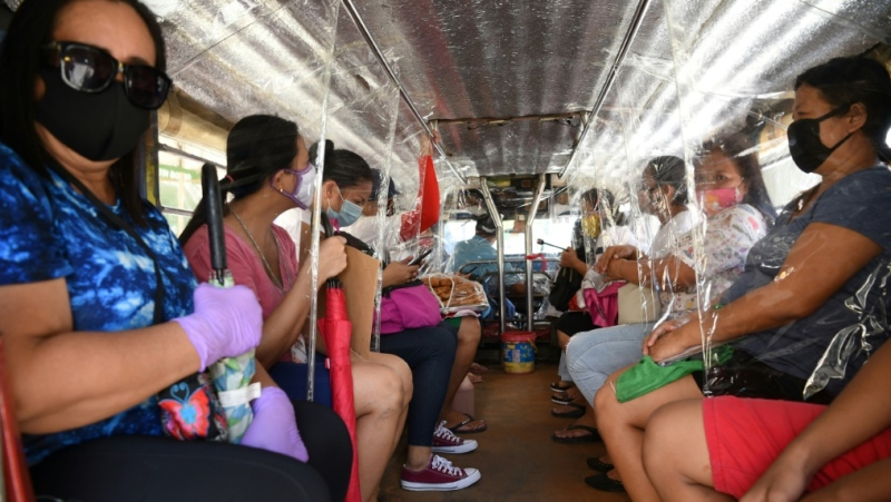 Passengers travel on a jeepney with seat dividers to ensure social distancing in Manila. Residents of Navotas, one of the poorest areas of the capital, will go back into lockdown following a spike in new coronavirus cases.  (AFP)