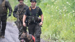 A K9 unit and other police officers search a back road on Saturday, July 11, 2020 in Saint-Apollinaire, Quebec. THE CANADIAN PRESS/Jacques Boissinot