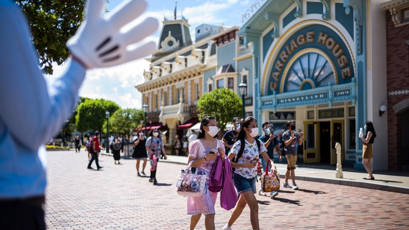 A cast member (L) welcomes visitors upon their arrival at Hong Kong's Disneyland on June 18, 2020, after the theme park officially reopened following nearly five months of closure in a fresh boost for a city that has largely managed to defeat the COVID-19 coronavirus. (Anthony Wallace/AFP/Getty Images/CNN)