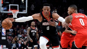 In this Jan. 29, 2020, file photo, Houston Rockets guard Russell Westbrook, left, dribbles next to Portland Trail Blazers guard Damian Lillard, right, during the first half of an NBA basketball game in Portland, Ore. Westbrook said Monday, July 13, 2020, that he has tested positive for coronavirus, and that he plans to eventually join his team at the restart of the NBA season. Westbrook made the revelation on social media. As recently as Sunday, the Rockets believed that Westbrook and James Harden — neither of whom traveled with the team to Walt Disney World near Orlando last week — would be with the team in the next few days. In Westbrook's case, that now seems most unlikely. (AP Photo/Steve Dykes, File)