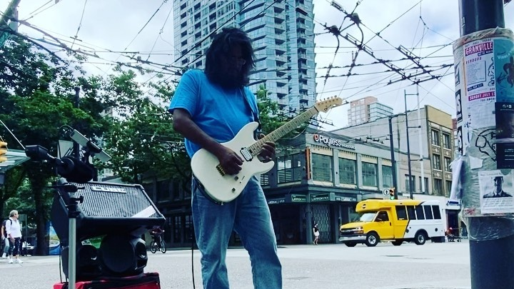 Marcel Greer plays guitar on Vancouver's busy Granville Street.