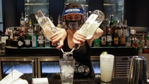 In this July 1, 2020, file photo, a bartender mixes a drink while wearing a mask and face shield at Slater's 50/50 in Santa Clarita, Calif. California Gov. Gavin Newsom on Monday, July 13, 2020, extended the closure of bars and indoor dining statewide and ordered gyms, churches and hair salons closed in most places as coronavirus cases keep rising in the nation's most populated state. (AP / Marcio Jose Sanchez, File)