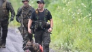 A K9 unit and other police officers search a back road on Saturday, July 11, 2020 in Saint-Apollinaire, Quebec. Quebec provincial police say two girls who were the subject of an Amber Alert have been found dead. THE CANADIAN PRESS/Jacques Boissinot