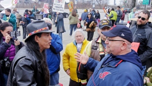 In this April 10, 2015, file photo, Philip Yenyo, left, executive director of the American Indians Movement for Ohio, talks with a Cleveland Indians fan before a baseball game against the Detroit Tigers, in Cleveland. (AP Photo/Mark Duncan, File)
