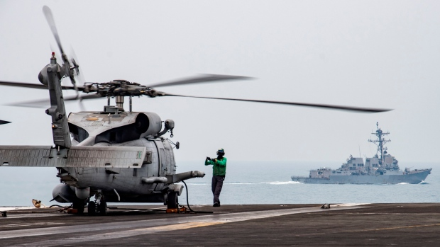 In this photo provided by U.S. Navy, Aviation Electronics Technician 3rd Class James Benzel, from Louisville, Ohio, assigned to the Saberhawks of Helicopter Maritime Strike Squadron, signals an MH-60R Sea Hawk to disengage its rotors on the flight deck of the USS Ronald Reagan (CVN 76) as USS Mustin (DDG 89) steams alongside in South China Sea, Thursday, July 9, 2020. (Mass Communication Specialist 3rd Class Erica Bechard/U.S.Navy via AP)