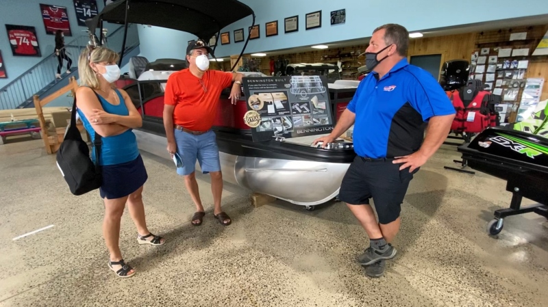 Orleans Boat World & Sports owner Marc Savage helping Andre Jette and Monica Clayton shop for a boat. Ottawa, ON. July 13, 2020. (Tyler Fleming / CTV News)