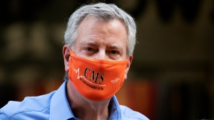 New York Mayor Bill de Blasio wears a mask while painting Black Lives Matter on Fifth Avenue in front of Trump Tower, on July 9, 2020, in New York. (Mark Lennihan / AP)