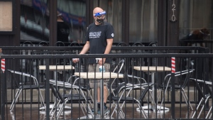 A man wears protective gear as he cleans the outdoor terrace of a pub in Montreal, Saturday, July 11, 2020, as the COVID-19 pandemic continues in Canada and around the world. THE CANADIAN PRESS/Graham Hughes
