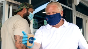 Ontario Premier Doug Ford hands a drink to a member of the media as he visits a bakery in Toronto, on Friday, July 10, 2020. (THE CANADIAN PRESS/Chris Young)