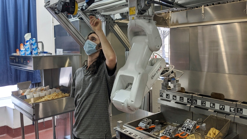 A technician makes an adjustment to a robot at Miso Robotics' White Castle test kitchen in Pasadena, Calif., Thursday, July 9, 2020. (Miso Robotics via AP)