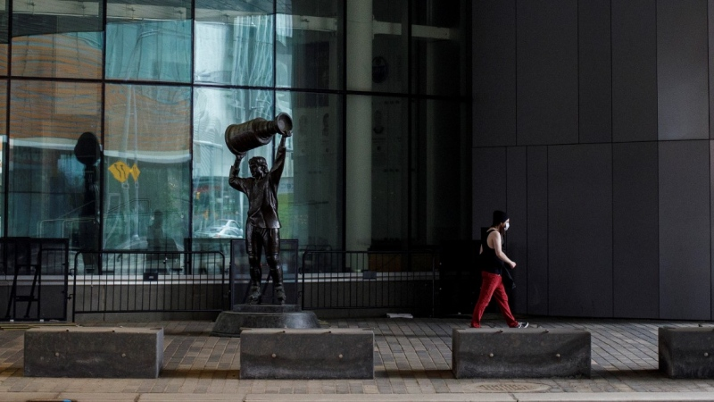 A pedestrian walks past the Wayne Gretzky statue at the home of the Edmonton Oilers, Rogers Place arena in Edmonton, Alta., on Thursday July 2, 2020. THE CANADIAN PRESS/Jason Franson