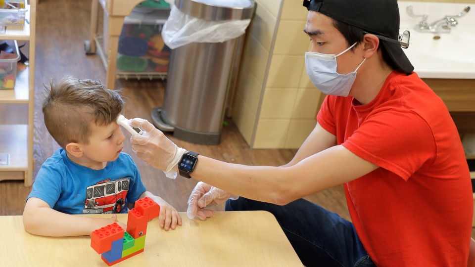 In this May 27, 2020 photo, a teacher at a daycare centre in Tacoma, Wash., wears a mask as he takes the temperature of a four-year-old boy. (AP Photo/Ted S. Warren)