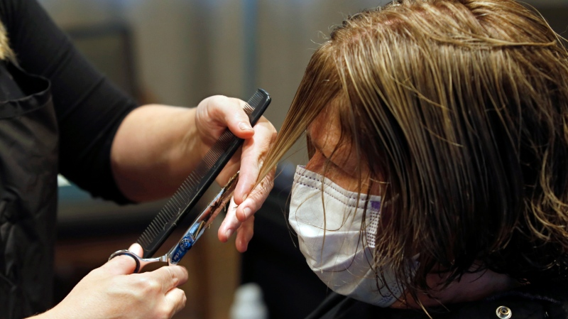 A woman gets her bangs trimmed at a sSalon in Auburn, Calif., Wednesday, May 27, 2020. (AP Photo/Rich Pedroncelli)