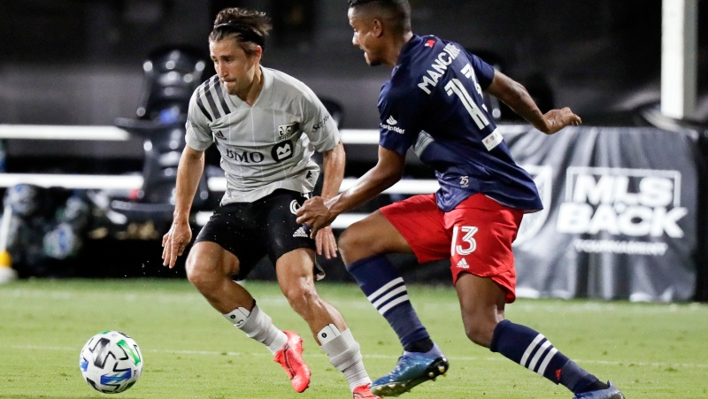 Montreal Impact's Bojan, left, makes a move to get past New England Revolution's Michael Mancienne (13) during the second half of an MLS soccer match in Kissimmee, Fla., Thursday, July 9, 2020. THE CANADIAN PRESS/AP-John Raoux