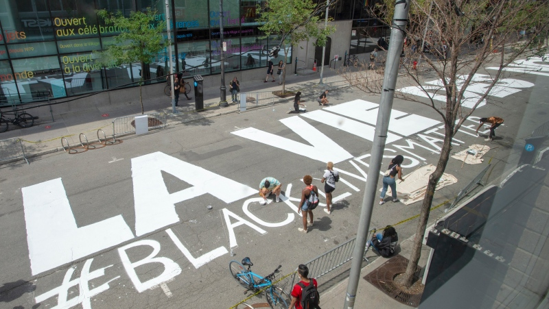 People paint Black Lives Matter if English and French on Ste. Catherine Street Tuesday July 14, 2020 in Montreal.THE CANADIAN PRESS/Ryan Remiorz
