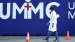 A healthcare worker walks across the parking lot of a COVID-19 testing site at United Memorial Medical Center Tuesday, July 14, 2020, in Houston. (AP / David J. Phillip)