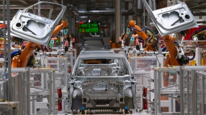 FILE- In this Tuesday, Feb. 25, 2020 file photo, robots work on an electric car ID.3 body at the assembly line during a press tour at the plant of the German manufacturer Volkswagen AG (VW) in Zwickau, Germany. (AP Photo/Jens Meyer, file)