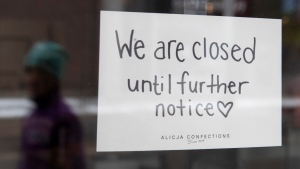 A sign on a shop window indicates the store is closed in Ottawa, on March 23, 2020. (Adrian Wyld / THE CANADIAN PRESS)