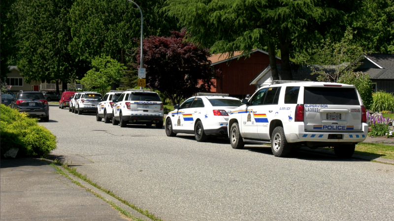 Police cruisers are parked near the scene of a suspicious death and brush fire on the Surrey-Langley border on Wednesday, July 15, 2020. (Jordan Jiang / CTV News Vancouver)