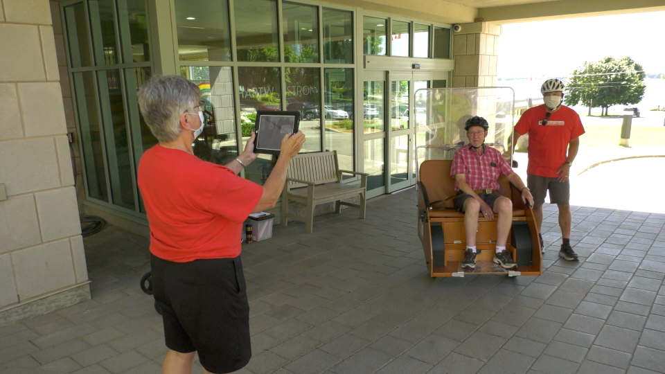 Cycling Without Age volunteer JoAnn Bell takes a photo of local senior Handy Nevers (centre) and volunteer/trishaw pilot Greg McElrea July 15, 2020. (Nate Vandermeer / CTV News Ottawa)