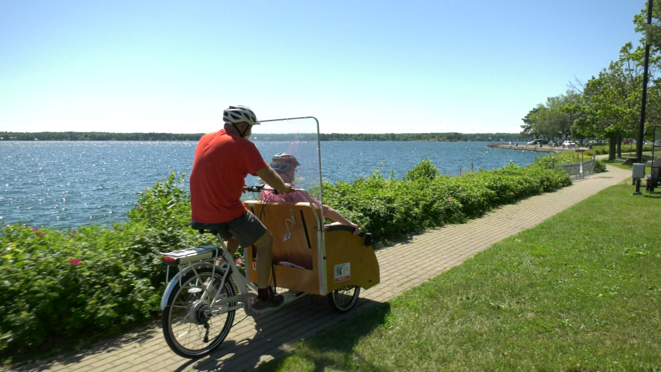 Greg McElrea pilots a trishaw carrying Handy Nevers along river in Brockville, ON. (Nate Vandermeer / CTV News Ottawa)