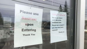 Signs are seen in the front window of Great West Auto Electric (Bumper to Bumper) in Swift Current. Many businesses in the city are taking extra precautions after multiple people who tested positive for COVID-19 visited various businesses. (Stefanie Davis/CTV News)