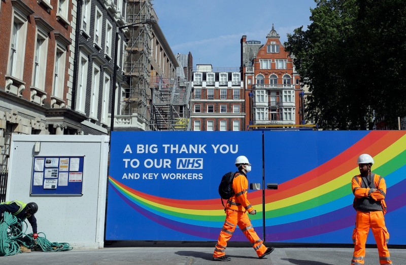 In this Thursday, May 7, 2020 file photo, a construction worker passes a sign thanking the NHS in London, as the country in is lockdown to prevent the spread of coronavirus. (AP Photo/Kirsty Wigglesworth, File)