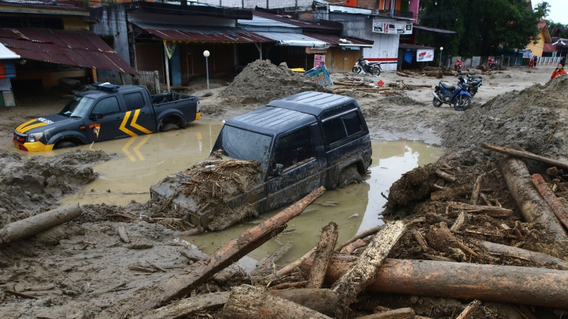 Cars are stuck in mud at an area affected by flash flood in Masamba, South Sulawesi province, Indonesia, Wednesday, July 15, 2020. (AP Photo/Khaizuran Muchtamir)