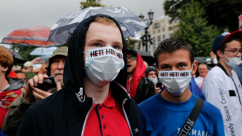 "People gather to collect signatures to cancel the results of voting on amendments to the Constitution in Moscow, Russia, Wednesday, July 15, 2020.  Writing on the face masks reads ""no"". (AP Photo/Alexander Zemlianichenko)"