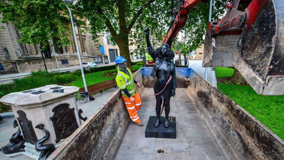 Contractors remove the statue 'A Surge of Power (Jen Reid) 2020' by artist Marc Quinn, which had been installed on the site of the fallen statue of the slave trader Edward Colston, in Bristol, England, on July 16, 2020. (Ben Birchall / PA via AP)