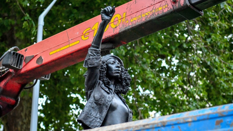 Contractors remove the statue 'A Surge of Power (Jen Reid) 2020' by artist Marc Quinn, which had been installed on the site of the fallen statue of the slave trader Edward Colston, in Bristol, on July 16, 2020. (Ben Birchall / PA via AP)