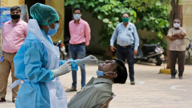A health worker takes a nasal swab sample of a man at an urban health centre in Ahmedabad, India, on July 16, 2020. (Ajit Solanki / AP)