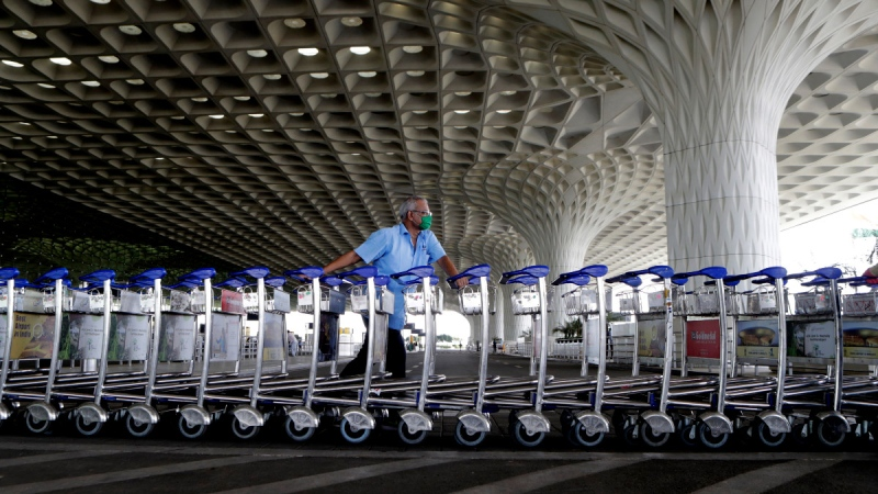 Airport staff push trollies at Chhatrapati Shivaji International Airport in Mumbai, India, on May 25, 2020. (Rajanish Kakade / AP)