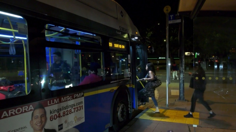 People board a transit bus at night in Metro Vancouver.