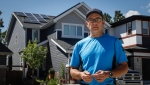 Electrician Fred Duplessis, who has installed 32 solar panels on the roof of his house, stands in front of his house in Calgary, Alta., Tuesday, July 14, 2020. (THE CANADIAN PRESS/Jeff McIntosh)