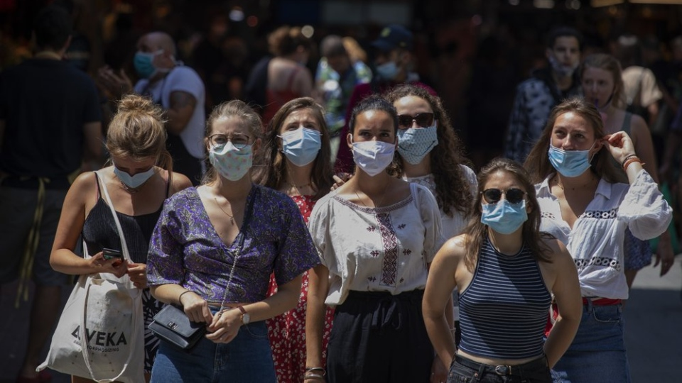 Tourists wearing face masks wait to cross a road in downtown Barcelona, Spain, Thursday, July 16, 2020. (AP Photo/Emilio Morenatti)