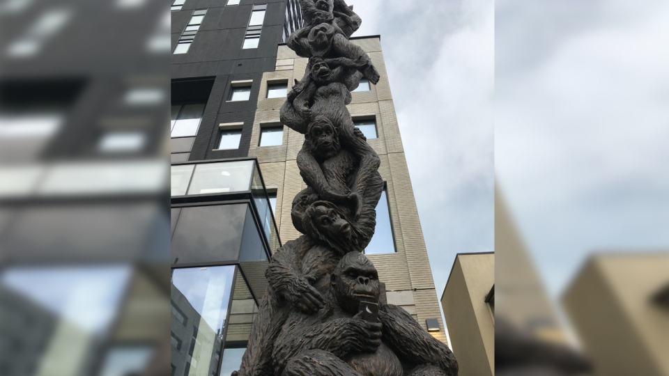 A tower of primates in front of a condo