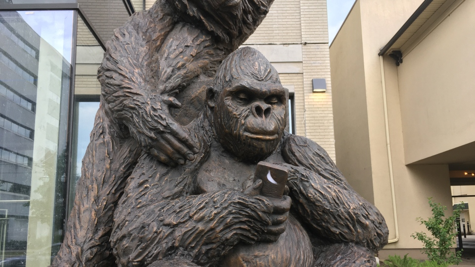 A sculpture of a gorilla holding a phone