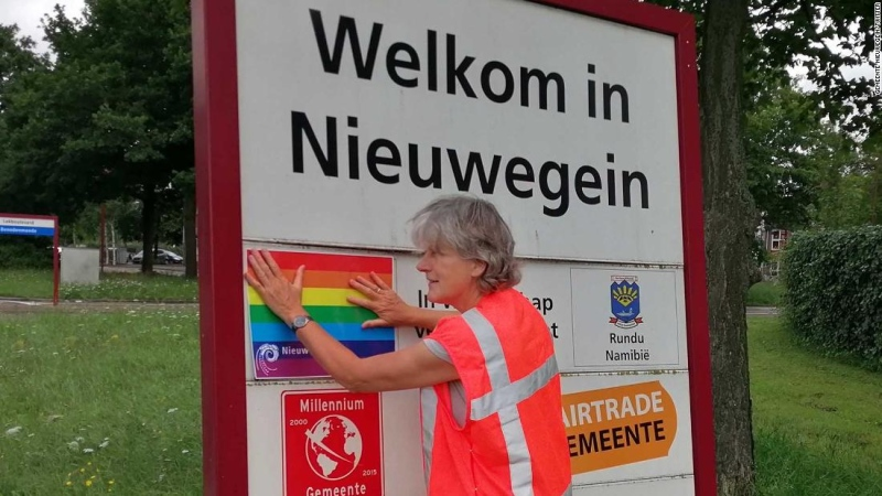 Nieuwegein alderman Marieke Schouten places a rainbow sticker over a sign announcing the relationship between the city and Pulawy. (Gemeente Nieuwegein/Twitter)