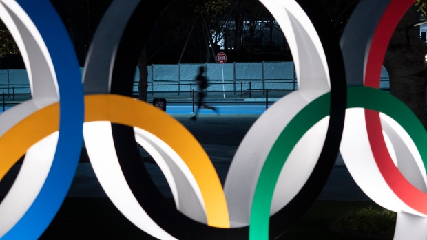 In this March 30, 2020, file photo, a man jogs past the Olympic rings in Tokyo. (AP Photo/Jae C. Hong, File)